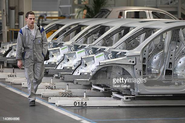 A worker walks by car bodies at the Volkswagen factory on March 7 2012 in Wolfsburg Germany In 2011 Volkswagen achieved record results with profits...