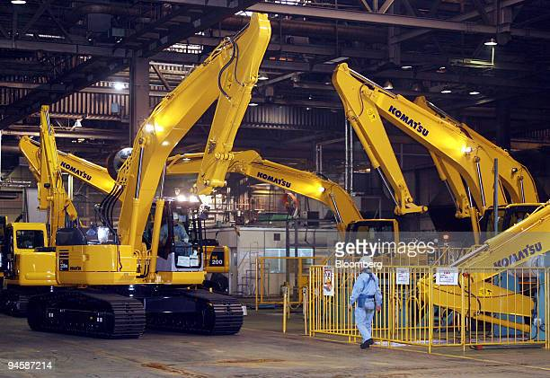 A worker walks by Komatsu Ltd hydraulic excavators at the company's Osaka Plant in Osaka Japan on Monday Jan 29 2007 Komatsu Ltd the world's...