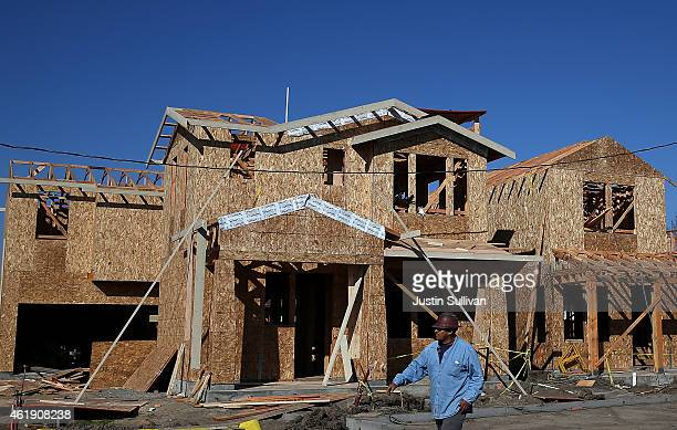 A worker walks by new homes that are under construction at a housing development on January 21 2015 in Petaluma California According to a Commerce...