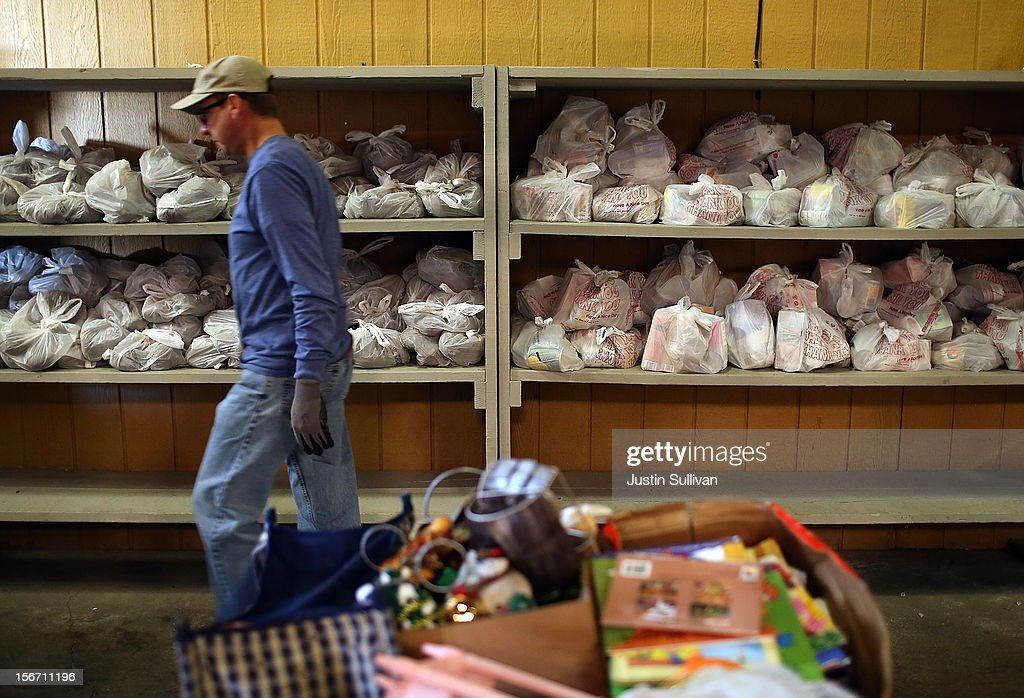 A worker walks by shelves of bagged canned goods at the Bay Area Rescue Mission on November 19, 2012 in Richmond, California. Days ahead of Thanksgiving, the Bay Area Rescue Mission received a donation of 320 turkeys and 60 hams from local business Bay Alarm that will be used to feed a holiday meal to needy and underpriviledged people.