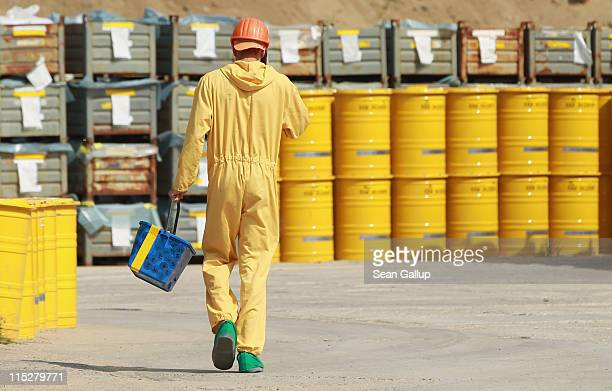 A worker walks by yellow barrels containing potentially radioactive material at the former Rheinsberg nuclear power plant on June 6 2011 in...