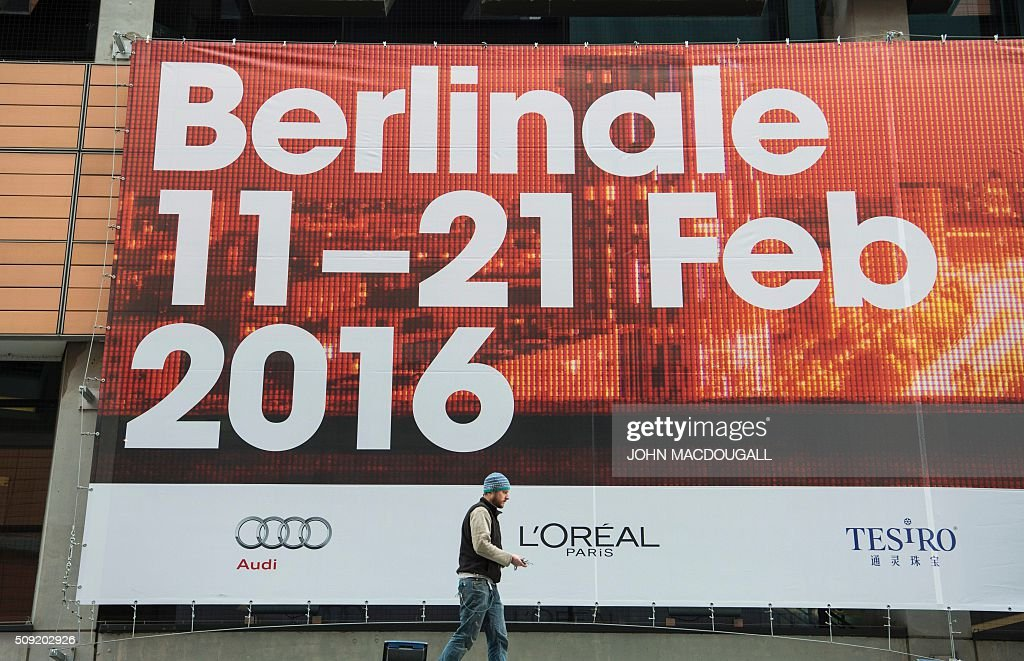 A worker walks in front of a giant billboard advertising the Berlinale Film Festival as he finishes putting it into place at a movie theatre in Berlin on February 9, 2016. The 66th Berlin film festival starts February 11 with a spotlight on Europe's refugee crisis. / AFP / John MACDOUGALL