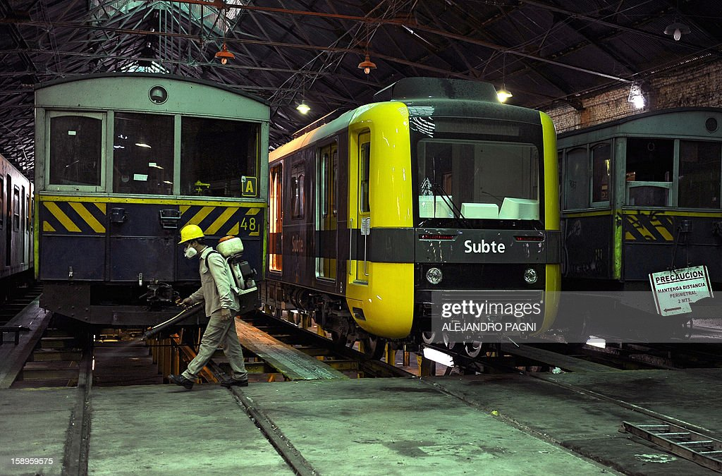 A worker walks near a historic wagons of La Brugeoise (L) and a new Chinese wagon that remain parked at the garage El Polvorin, in the neighborhood of Caballito, Buenos Aires on January 4, 2013. The Line A will be closed betwen January 12 and March 8 following a decision by Buenos Aires city Mayor Mauricio Macri to replace the fleet with Chinese-made wagons. Line A was the first subway line to work in the southern hemisphere and its trains are among the ten oldest still working daily. The La Brugeoise wagons were constructed between 1912 and 1919 by La Brugeoise et Nicaise et Delcuve in Belgium. AFP PHOTO / ALEJANDRO PAGNI