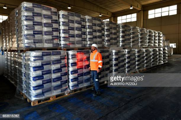 A worker walks near a shipment of French sugar cooperative Cristal Union at the SFIR Raffineria di Brindisi sugar refinery in Brindisi on March 15...