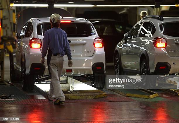 A worker walks near Fuji Heavy Industries Ltd Subaru XV vehicles on the production line at the company's Gunma Yajima Plant in Ota City Gunma...
