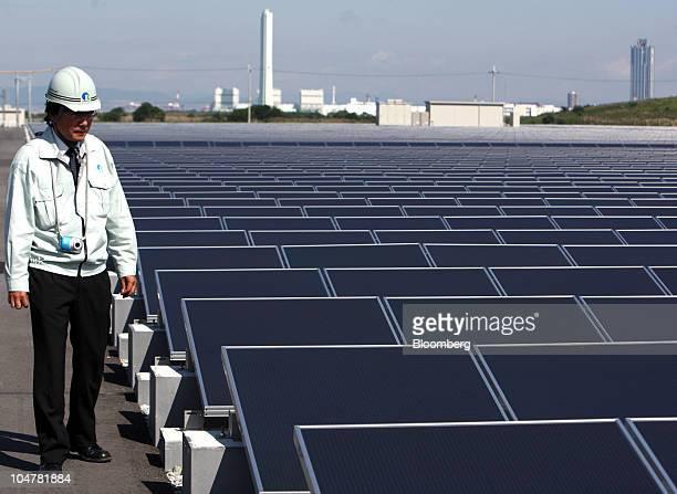 A worker walks near solar panels manufactured by Sharp Corp at Kansai Electric Power Co's mega solar power station in Sakai City Osaka Japan on...