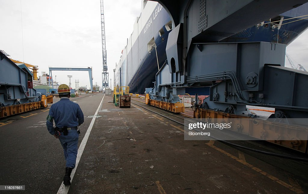 A worker walks near the Nippon Yusen K.K.'s car transporter ship, Auriga Leader, at Mitsubishi Heavy Industries Ltd.'s Honmoku plant in Yokohama city, Kanagawa prefecture, Japan, on Wednesday, June 15, 2011. Nippon Yusen K.K. is Japan's largest shipping line. Photographer: Tomohiro Ohsumi/Bloomberg via Getty Images