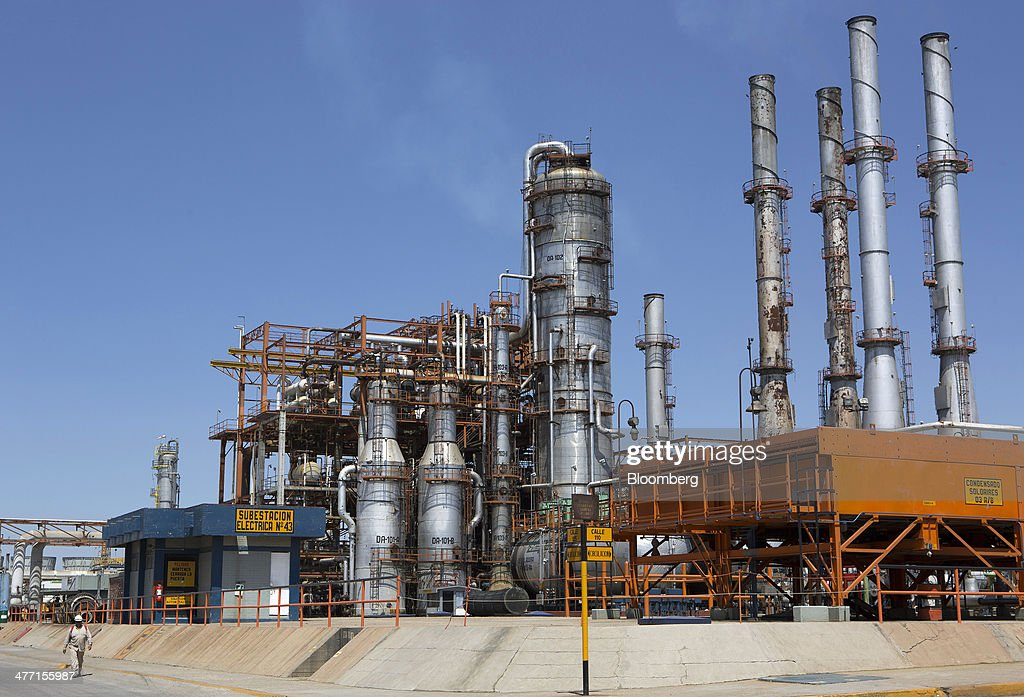 A worker walks next to an electrical substation at the Petroleos Mexicanos Miguel Hidalgo Refinery in Tula de Allende Mexico on Thursday March 6 2014...