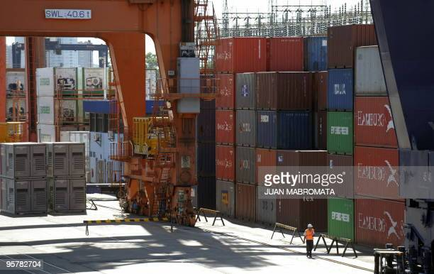 A worker walks next to containers at Buenos Aires harbour on January 14 2009 AFP PHOTO / Juan Mabromata