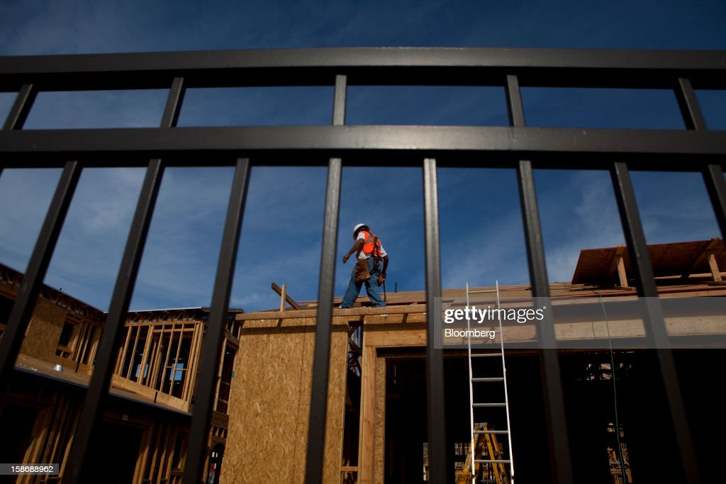 A worker walks on the roof of a house under construction at Davidson Communities LLC's Arista at The Crosby development in Rancho Santa Fe, California, U.S., on Friday, Dec. 21, 2012. New home sales climbed to a 380,000 annual rate in November, the most since April 2010, according to the median forecast of 60 economists surveyed by Bloomberg before Dec. 27 figures from the Commerce Department. Photographer: Sam Hodgson/Bloomberg via Getty Images