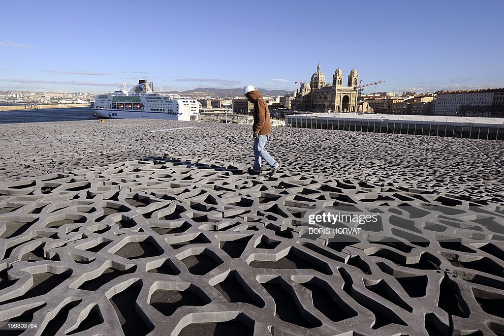 A worker walks on the roof of the Museum of Civilizations from Europe and the Mediterranean (MuCEM), designed by Italian architect Rudy Ricciotti, on January 11, 2013 in Marseille. Long plagued by a reputation for gang crime and lawlessness, France's port city of Marseille is hoping its year as the 2013 European Capital of Culture will finally give its image a makeover. The gritty Mediterranean city will kick off the festivities on January 12, 2013 with a downtown parade, fireworks and the opening of a slew of exhibitions. At background, a ferry and Sainte-Marie Majeure cathedral also known as 'La Major'. AFP PHOTO / BORIS HORVAT