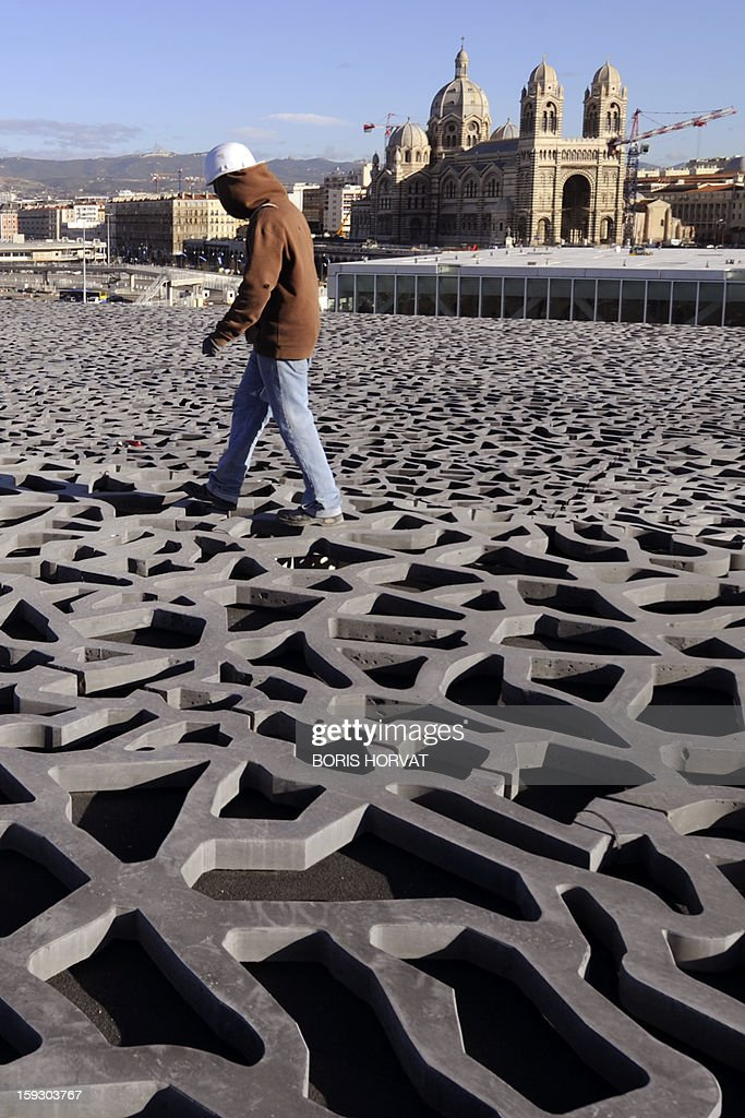A worker walks on the roof of the Museum of Civilizations from Europe and the Mediterranean (MuCEM), designed by Italian architect Rudy Ricciotti, on January 11, 2013 in Marseille. Long plagued by a reputation for gang crime and lawlessness, France's port city of Marseille is hoping its year as the 2013 European Capital of Culture will finally give its image a makeover. The gritty Mediterranean city will kick off the festivities on January 12, 2013 with a downtown parade, fireworks and the opening of a slew of exhibitions. At background, Sainte-Marie Majeure cathedral also known as 'La Major'.
