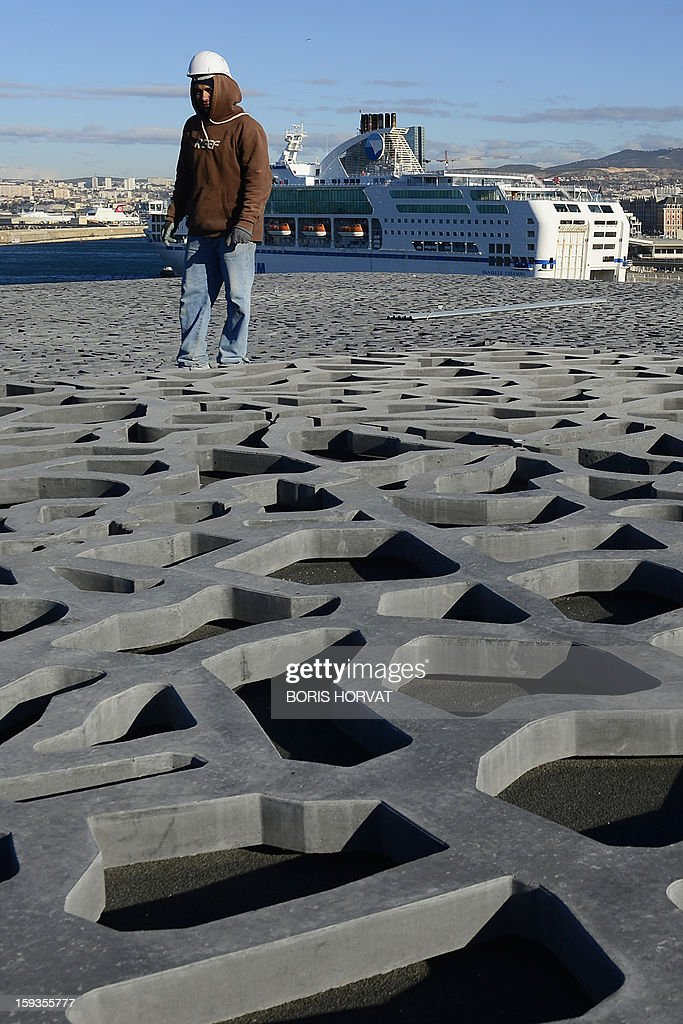 A worker walks on the roof of the Museum of Civilizations from Europe and the Mediterranean (MuCEM), designed by Italian architect Rudy Ricciotti, on January 11, 2013 in Marseille. Long plagued by a reputation for gang crime and lawlessness, France's port city of Marseille is hoping its year as the 2013 European Capital of Culture will finally give its image a makeover. The gritty Mediterranean city will kick off the festivities on January 12, 2013 with a downtown parade, fireworks and the opening of a slew of exhibitions. At background, a ferry in the harbour. AFP PHOTO / BORIS HORVAT