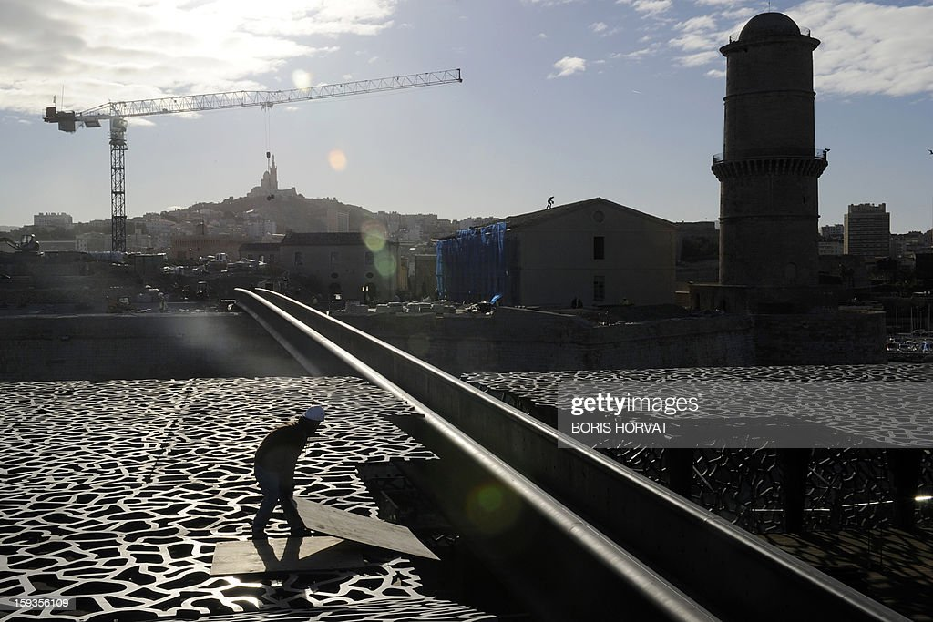 A worker walks on the roof of the Museum of Civilizations from Europe and the Mediterranean (MuCEM), designed by Italian architect Rudy Ricciotti, on January 11, 2013 in Marseille. Long plagued by a reputation for gang crime and lawlessness, France's port city of Marseille is hoping its year as the 2013 European Capital of Culture will finally give its image a makeover. The gritty Mediterranean city will kick off the festivities on January 12, 2013 with a downtown parade, fireworks and the opening of a slew of exhibitions. At background, a ferry and Sainte-Marie Majeure cathedral also known as 'La Major'.
