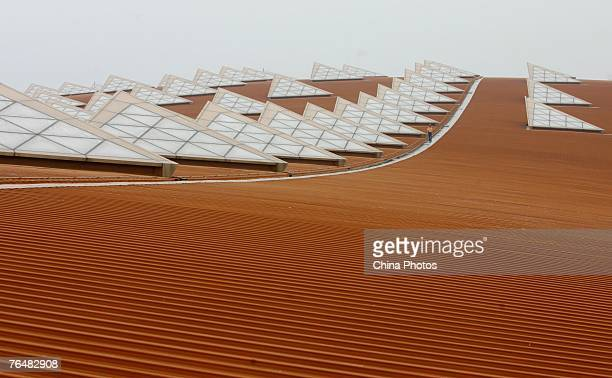 A worker walks on the roof of the new terminal building T3 under construction at the Beijing Capital International Airport on August 28 2007 in...