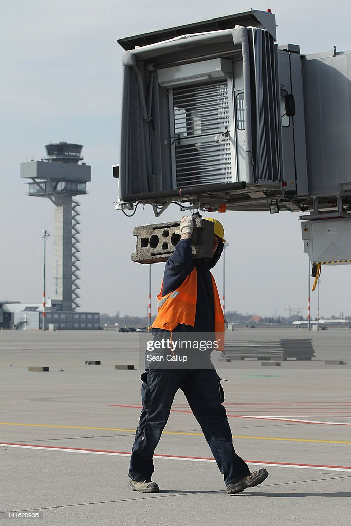 A worker walks on the tarmac as the control tower stands behind at Willy Brandt Berlin Brandenburg International Airport on March 20, 2012 in Berlin, Germany. The new airport, which will replace the city's current Tegel and Schoenefeld airports, will officially open in May and begin operaiton on June 3.