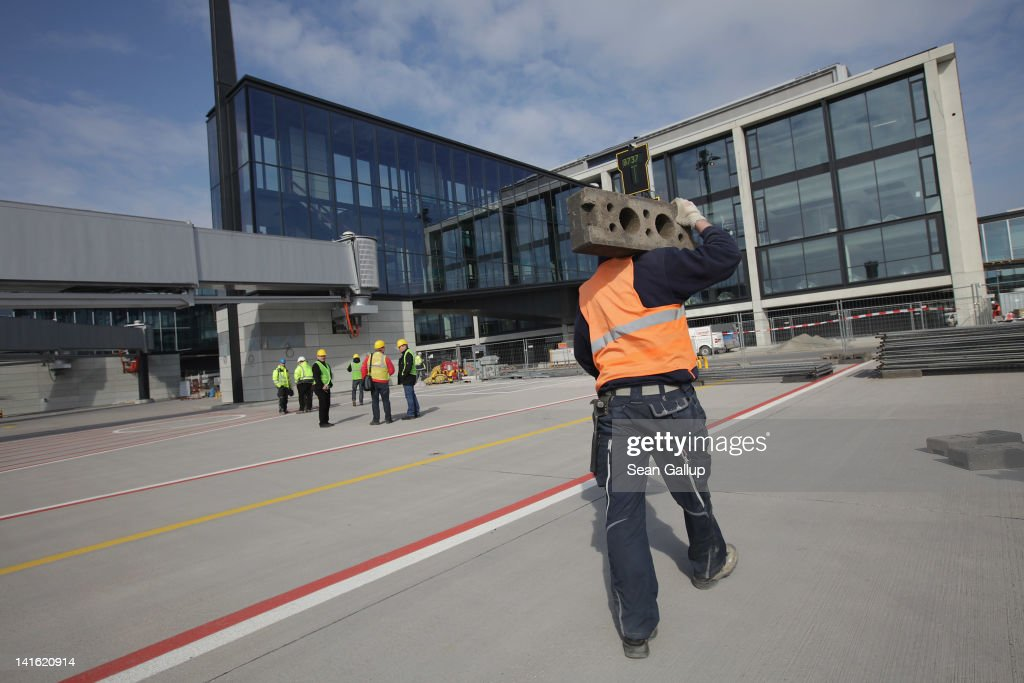 A worker walks on the tarmac at Willy Brandt Berlin Brandenburg International Airport on March 20, 2012 in Berlin, Germany. The new airport, which will replace the city's current Tegel and Schoenefeld airports, will officially open in May and begin operaiton on June 3.
