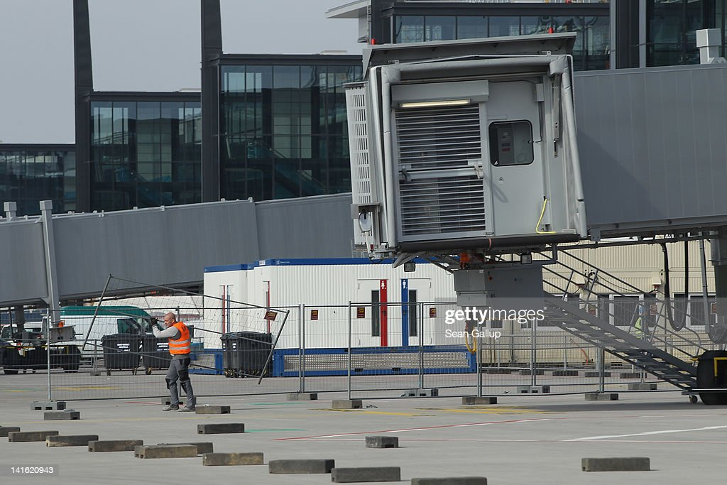 A worker walks on the tarmac next to jetways at Willy Brandt Berlin Brandenburg International Airport on March 20, 2012 in Berlin, Germany. The new airport, which will replace the city's current Tegel and Schoenefeld airports, will officially open in May and begin operation on June 3.