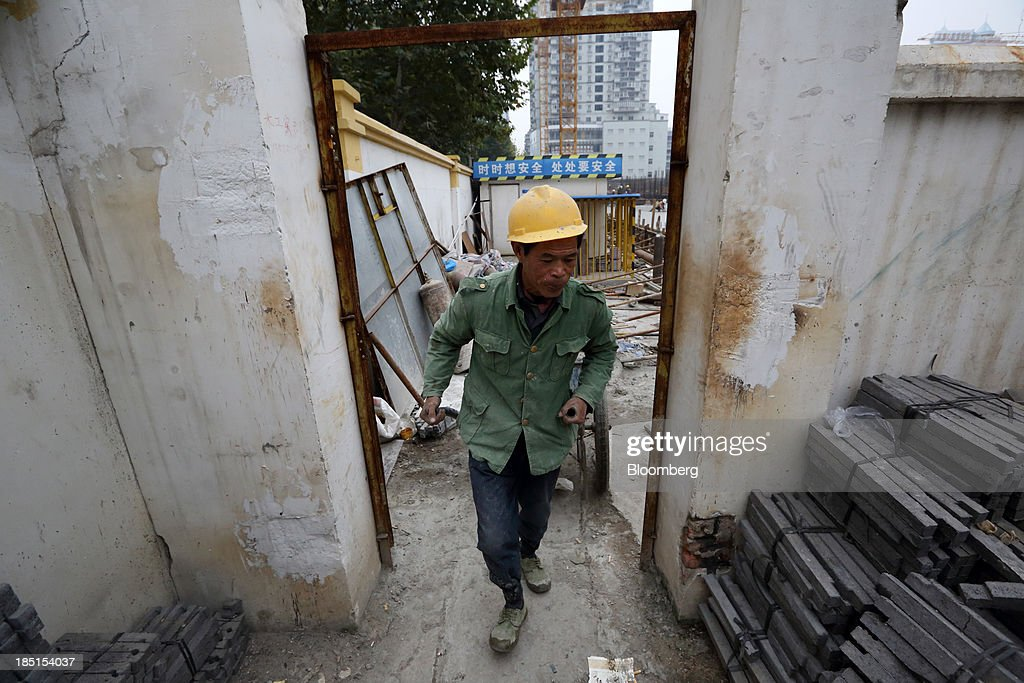 A worker walks out of a construction site for a residential property in Wuhan, China, on Thursday, Oct. 17, 2013. China is scheduled to release third-quarter gross domestic product figures on Oct. 18. Photographer: Tomohiro Ohsumi/Bloomberg via Getty Images