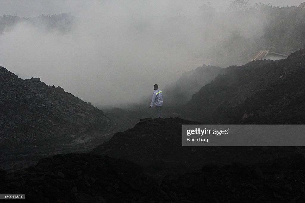 A worker walks over stockpiles of coal in the smoke at the PT Exploitasi Energi Indonesia open pit coal mine in Palaran, East Kalimantan province, Indonesia, on Friday Sept. 13, 2013. Prices of power-station coal in Indonesia, the worlds biggest exporter, may be little changed in coming weeks, according to Bloomberg News survey. Photographer: Dadang Tri/Bloomberg via Getty Images
