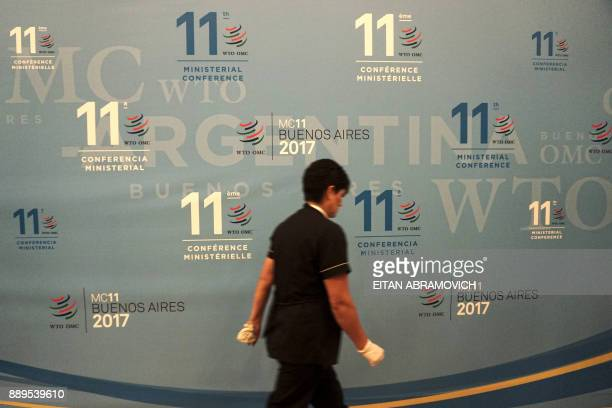 A worker walks past a banner at the 11th Ministerial Conference of the World Trade Organization in Buenos Aires Argentina on December 10 2017 / AFP...