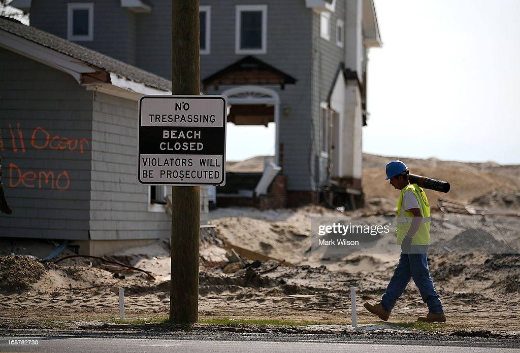A worker walks past a beach front home that was damaged by Superstorm Sandy and is sheduled to come down and be hauled away, May 15, 2013 in Manotoloking, New Jersey. Mantoloking officials say that at least 50 homes are scheduled to be demolished in the up coming weeks.