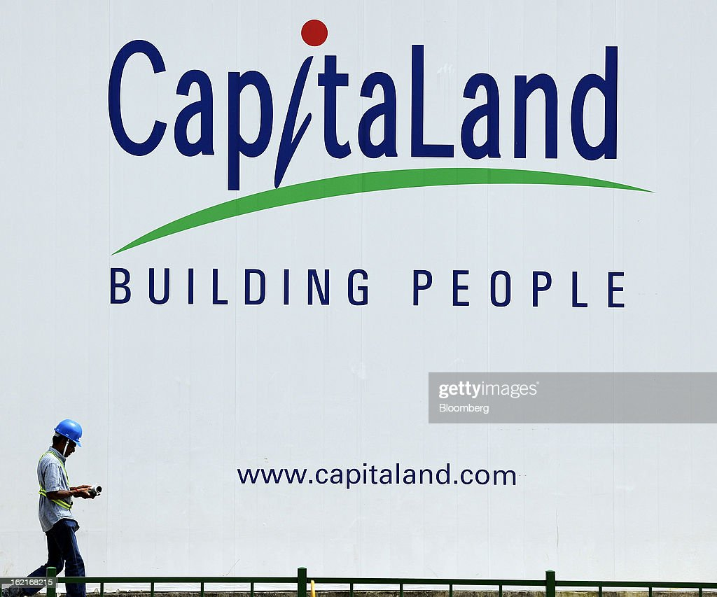 A worker walks past a billboard displaying CapitaLand Ltd. signage outside the company's Bedok Residences mixed development project construction site in Singapore, on Monday, Feb. 18, 2013. CapitaLand, Southeast Asia's biggest developer, is scheduled to release fourth quarter earnings on Feb. 21. Photographer: Munshi Ahmed/Bloomberg via Getty Images