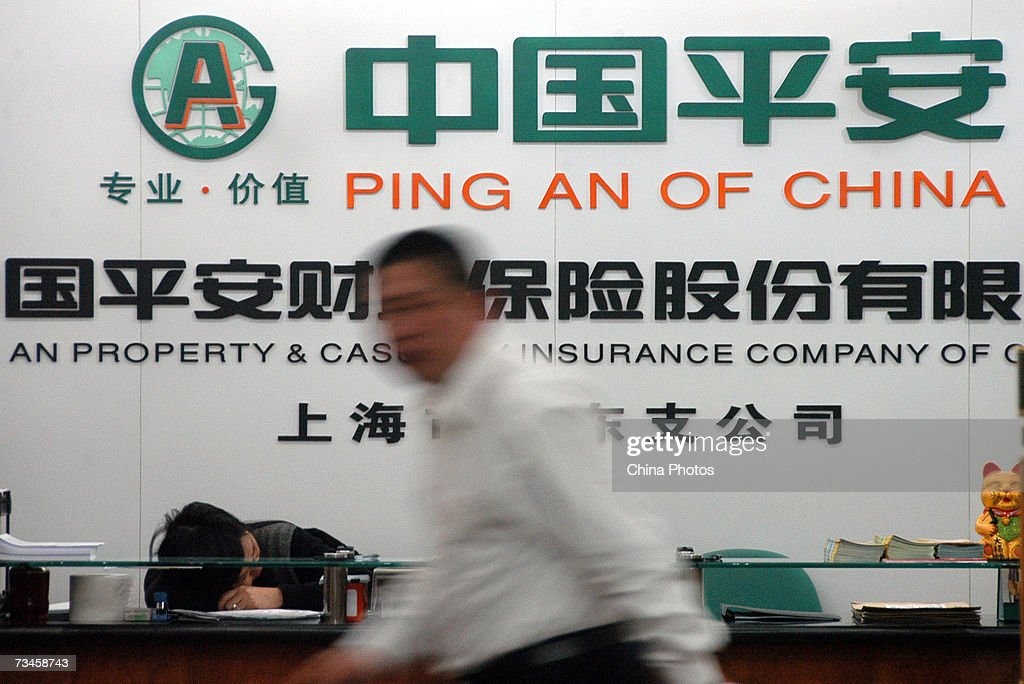 A worker walks past a board at Ping An Of China on March 1, 2007 in Nanjing of Jiangsu Province, China. Ping An Insurance, China's second-largest life insurer, saw its shares close at 47.92 yuan (5.99 U.S. dollars) per share on Thursday morning on its debut on the Shanghai stock exchange, down 4.16 percent from its opening price.