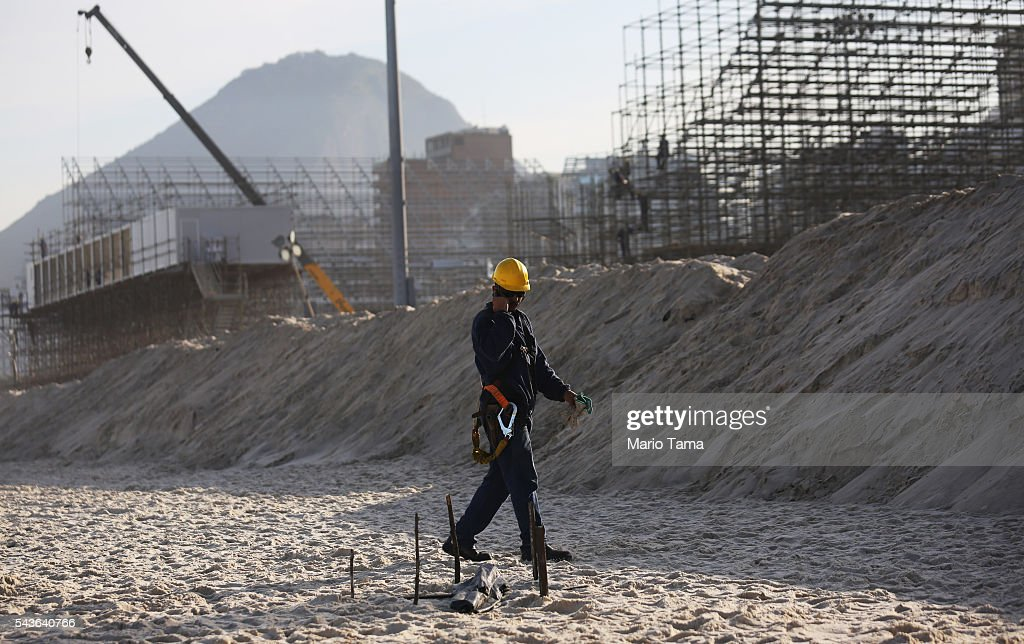A worker walks past a body part, covered in a plastic bag, which was discovered on Copacabana Beach near the Olympic beach volleyball venue on June 29, 2016 in Rio de Janeiro, Brazil. Parts of a mutilated body were discovered on the sands of the beach while it remains unknown how the person died. The Rio 2016 Olympic Games begin August 5 amidst an economic crisis in the country.