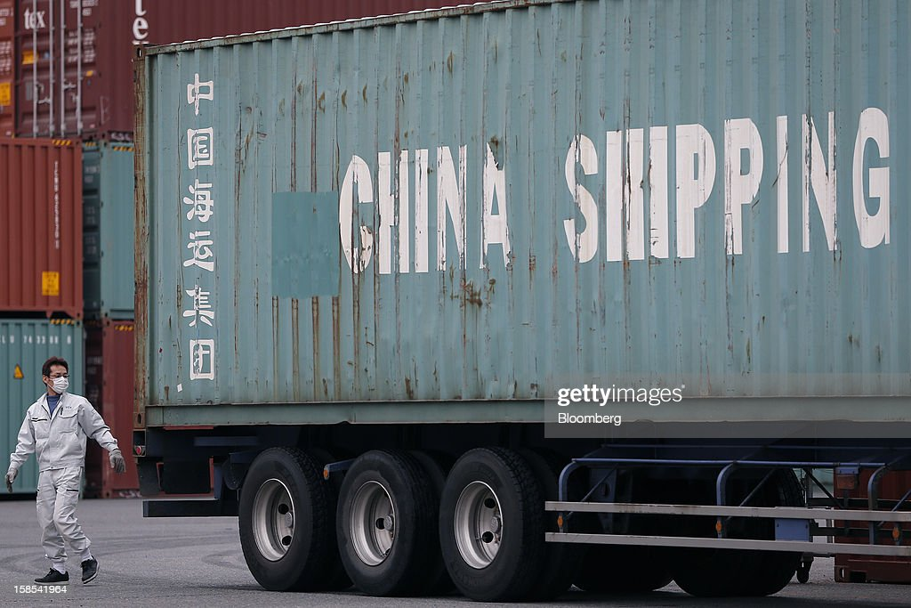 A worker walks past a China Shipping Container Lines Co. container on a truck at a container terminal in Tokyo, Japan, on Tuesday, Dec. 18, 2012. Japan's exports fell for a sixth month in November and the trade deficit swelled, underscoring the challenge that incoming Prime Minister Shinzo Abe faces in reviving growth. Photographer: Kiyoshi Ota/Bloomberg via Getty Images