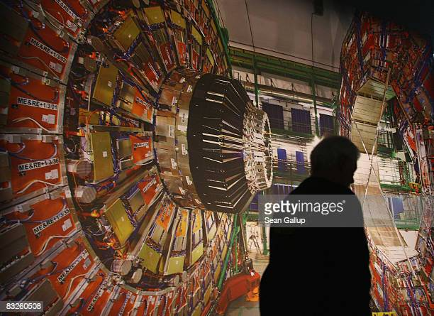 A worker walks past a giant photograph of the CMS detector of the Large Hadron Collider at the 'Weltmaschine ' exhibition on October 14 2008 in...