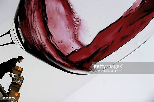A worker walks past a giant placard of a glass of wine on the first day of the 44th Vinitaly wine fair in Verona on April 8 2010 150000 visitors are...