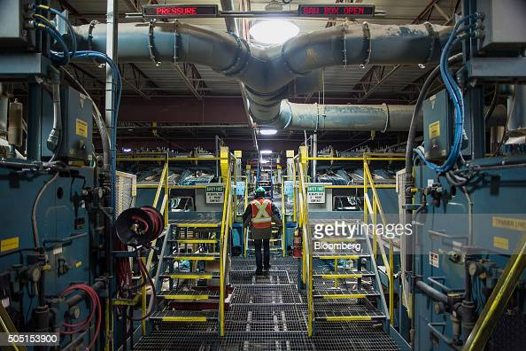 A worker walks past a machine that sorts lumber into grades and sizes at the Resolute Forest Products mill in Thunder Bay Canada Ontario on Friday...