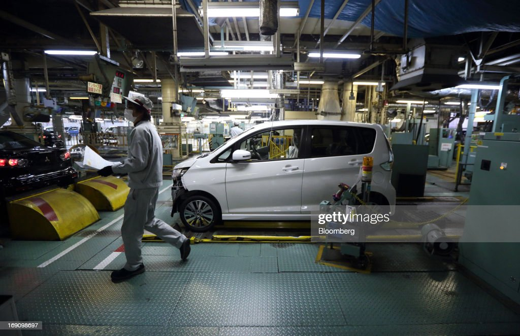 A worker walks past a minicar which will be sold as the Nissan DAYZ by Nissan Motor Co. and Mitsubishi eK Wagon by Mitsubishi Motors Corp. on the production line of the Mitsubishi Motors Mizushima plant in Kurashiki, Okayama Prefecture, Japan, on Monday, May 20, 2013. Nissan will start selling the first minicar it jointly developed with Mitsubishi Motors in Japan next month amid increasing demand from the nation's consumers for smaller and cheaper vehicles. Photographer: Tomohiro Ohsumi/Bloomberg via Getty Images