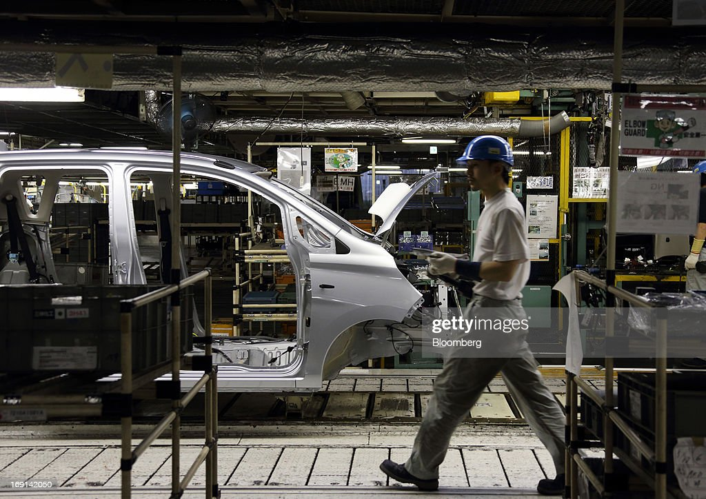 A worker walks past a minicar which will be sold as the Nissan DAYZ by Nissan Motor Co. and Mitsubishi eK Wagon by Mitsubishi Motors Corp. on the production line of the Mitsubishi Motors Mizushima plant in Kurashiki City, Okayama Prefecture, Japan, on Monday, May 20, 2013. Nissan will start selling the first minicar it jointly developed with Mitsubishi Motors in Japan next month amid increasing demand from the nation's consumers for smaller and cheaper vehicles. Photographer: Tomohiro Ohsumi/Bloomberg via Getty Images