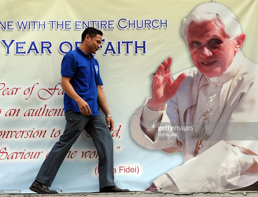 A worker walks past a portrait of Pope Benedict XVI displayed outside an office building in Manila on February 12, 2013. People across the mainly Catholic Philippines feel regret, gratitude and sympathy after Pope Benedict XVI announced plans on February 11 to resign, a presidential spokesman said. The Catholic Church entered uncharted waters on February 12 after Pope Benedict XVI's shock announcement that he would become the first pontiff to resign of his own free will in 700 years.