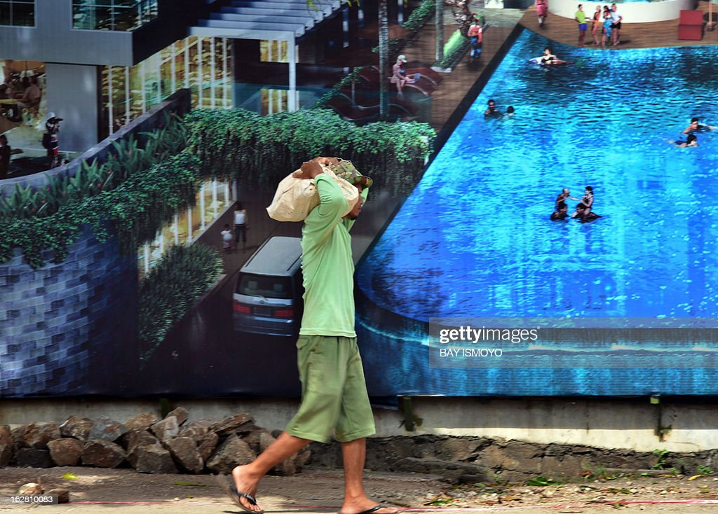 A worker walks past a poster of a newly built luxury residence in Jakarta on February 28, 2013. The government statistics show that the decrease in the official poverty rate is slowing — from 12.3 percent of all Indonesians in September 2011 to 11.7 percent a year later and in a speech to district leaders last week, Indonesian President Susilo Bambang Yudhoyono said job creation was the most effective way to reduce poverty. AFP PHOTO / Bay ISMOYO