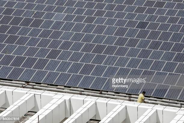 A worker walks past a rooftop solar farm at the BYD Co headquarters in Shenzhen China on Thursday Sept 21 2017 China will likely order an end to...