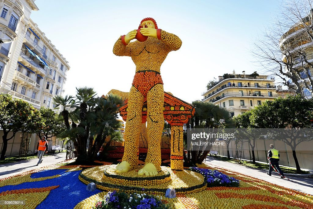 A worker walks past a sculpture decorated with oranges and lemons in Menton on the French Riviera on February 11, 2016, ahead of the start of the 'Fete du Citron' (Lemon Festival). The theme of this 83rd edition, running from February 13 until March 2, 2016, is called 'Cinecitta'. / AFP / VALERY HACHE