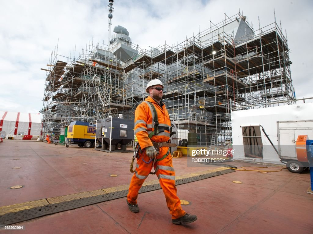 A worker walks past a section of the 65,000-tonne British aircraft carrier HMS Queen Elizabeth, under construction in Rosyth dockyard in Scotland, on May 24, 2016. / AFP / Robert Perry