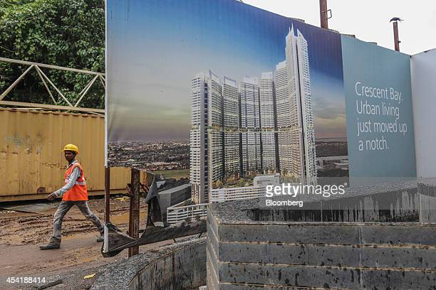 A worker walks past an advertisement for luxury residential towers at a construction site developed by Omkar Realtors Developers Pvt in the Parel...