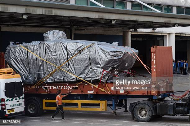 A worker walks past an impounded tarpaulincovered armoured troop carrier Terrex vehicle belonging to the Singapore military after it was placed by...