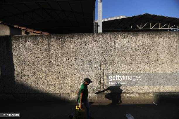 A worker walks past an industrial yard in the Caju neighbourhood which houses two forlorn shipyards along Guanabara Bay on August 8 2017 in Rio de...