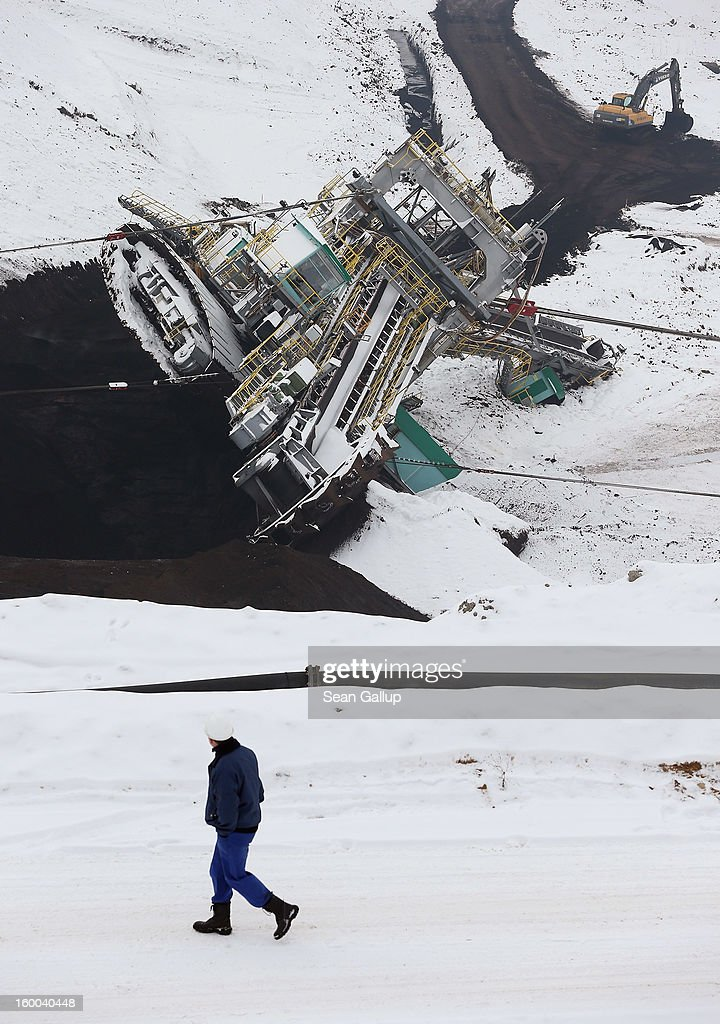 A worker walks past as colleagues attempt to set a 950-tonne bucket excavator upright over the course of several hours following an accident at an open-pit coal mine on January 25, 2013 near Deutzen, Germany. The bucket excavator tipped over last summer after plateaus of earth and sand nearby gave way, pushing a layer of coal underneath. The excavator had been lying severaly tilted to one side ever since at the Vereinigtes Schleenhain mine, which is operated by Mibrag. Open-pit lignite coal mines are still common across eastern Germany and produce coal for local electricity production.