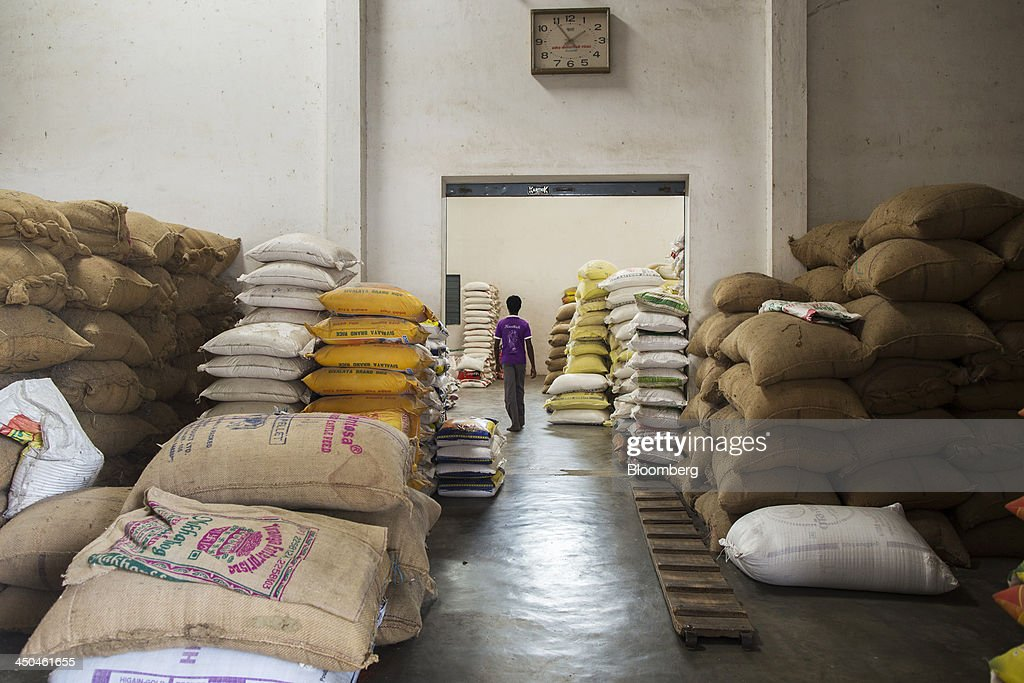 A worker walks past bags of rice in a warehouse at the KRK Modern Rice Mill in Kothapeta, Tamil Nadu, India, on Thursday, Nov. 14, 2013. Record onion prices and the soaring cost of rice and coriander are frustrating Reserve Bank of India Governor Raghuram Rajans battle to curb inflation while supporting growth in Asias third-largest economy. Photographer: Prashanth Vishwanathan/Bloomberg via Getty Images