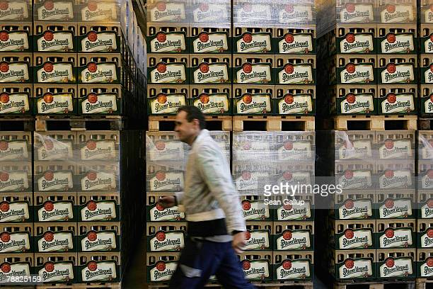 A worker walks past cases of freshlybrewed PilsnerUrquell lager beer at the Prazdroj brewery November 15 2006 in Pilsen Czech Republic Prazdroj along...