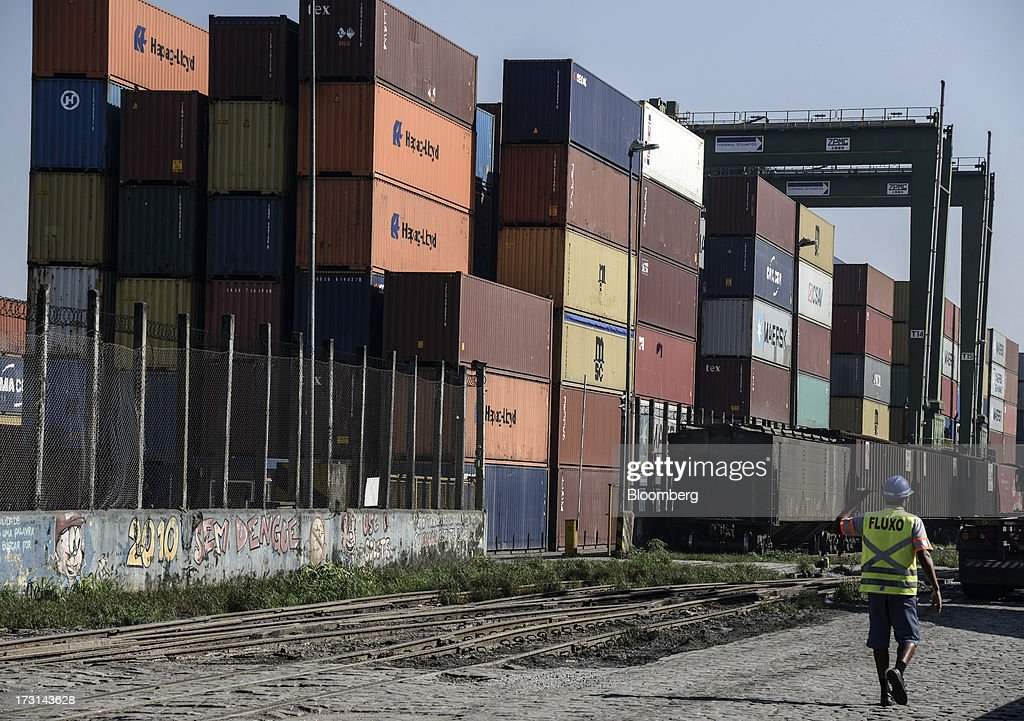 A worker walks past containers waiting to be loaded at the Port of Santos in Santos, Brazil, on Friday, July 5, 2013. Rising borrowing costs and the global bond selloff triggered by the prospect of reduced U.S. stimulus are prompting Brazilian investors to boost holdings of the countrys floating-rate securities. Photographer: Paulo Fridman/Bloomberg via Getty Images