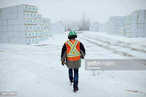 A worker walks past cut and finished lumber packaged in the mill yard in preparation for shipment at the Resolute Forest Products facility in Thunder...