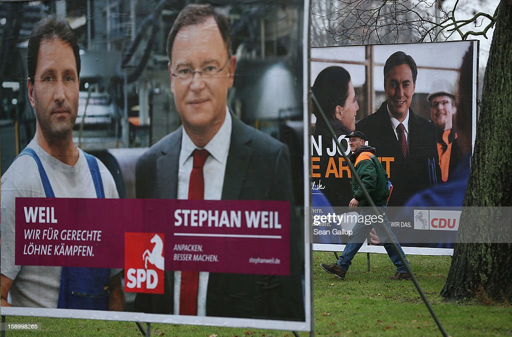 A worker walks past election campaign billboards featuring Hanover Mayor and German Social Democrats (SPD) candidate Stephan Weil (L) and Lower Saxony Governor and incumbent candidate of the German Christian Democrats (CDU) David McAllister on January 5, 2013 in Hanover, Germany. Lower Saxony is holding state elections on January 20 and many analysts see the election as a bellwether for national elections scheduled to take place later this year.