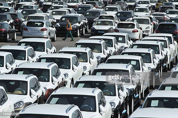 A worker walks past freshlyassembled Porsche Cayenne and Panamera cars standing on a parking lot before shipping at the Porsche factory on March 28...
